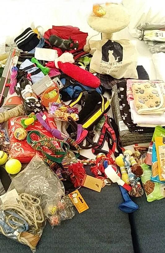 Bildet viser en mengde utstyr  til katter og hunder. Det er mange pledd, tennisballer, hundebånd og tyggeleker. Det er et lite klorestativ til katt, små poser med godis til hunder og et stort handlenett med teksten Dyrenes Hus. Det er et lite berg av gaver.