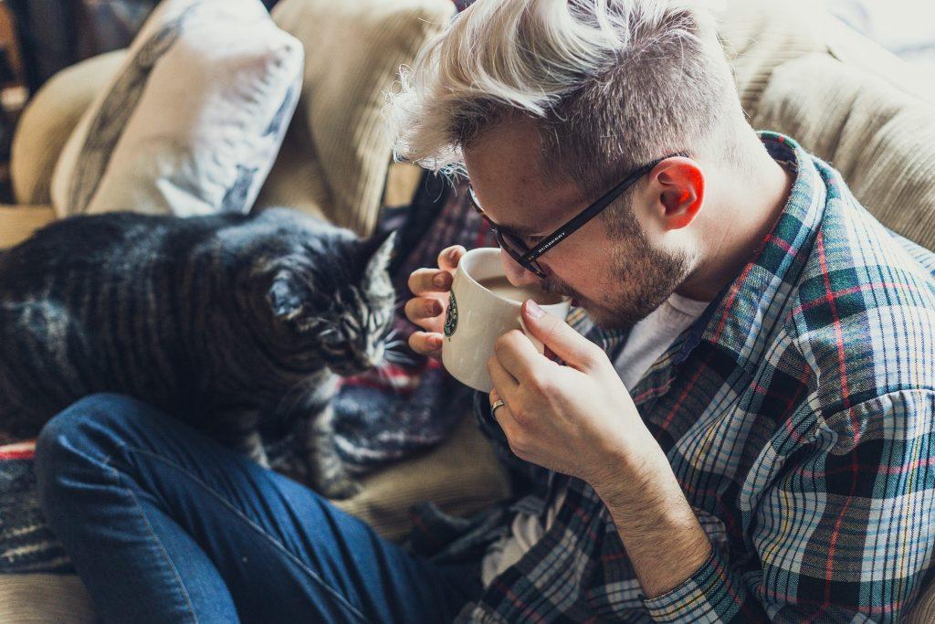 En mann med rutete skjorte og kort blondt hår med lang lugg sitter i sofaen og drikker fra en kopp, ved siden av ham er et en voksen tigerstripet katt.