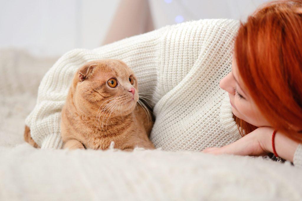 En rødhåret kvinne ligger på et kremefarget pledd og ser på sin røsfargede katt som ser tilbake på henne.